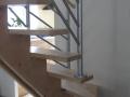 Escalier sur double crémaillère centrale en érable vernis incolore et garde corps en acier laqué.